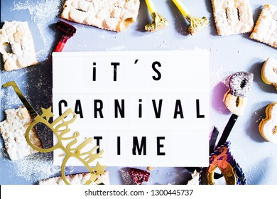 "Carnival concept, a lightbox with message "" it's carnival time"" illuminate circled by cookies and sweeties typical of carnival, like italian sfrappole or Chiacchiere, carnival fried pastry,flatlay"