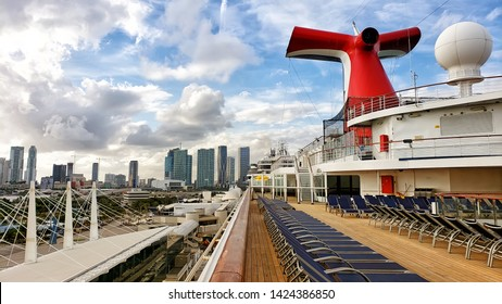 Carnival Cruise ship funnel in traditional red, white and blue compony colors. Open deck of the cruise ship.  chaise lounges on a deck in the morning. Nobody on a deck. Miami, may 23, 2019