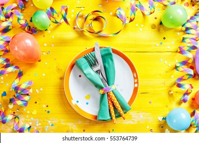 Carnival or Fasching cutlery and plate with fork and knife in overhead view on yellow party or birthday background table