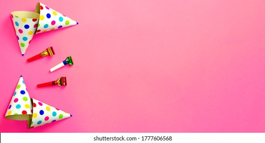Carnival hats and accessories for birthday celebration lie on bright pink background. Copy space for text. Top view. Flat lay. Lay out. Banner. Close-up. Holiday.