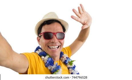 Carnival holiday, known as Carnaval in Brazil. Man taking a selfie. Brazilian. Vacation. He is wearing sunglasses and hat. Flower necklace. He is wearing a yellow jersey. Isolated on white background.