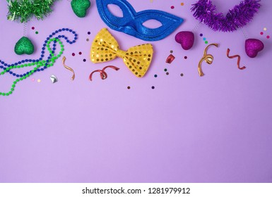 Carnival or mardi gras background with carnival masks, beards and photo booth props. Top view from above