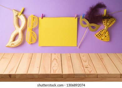Carnival, mardi gras or purim holiday background with empty wooden table, paper note and carnival mask.