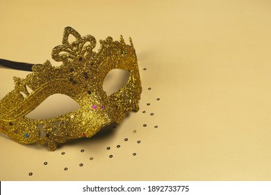 Carnival Mask with glitter on golden background. Festive party, Mardi gras or Purim holiday. Сopy space, close up