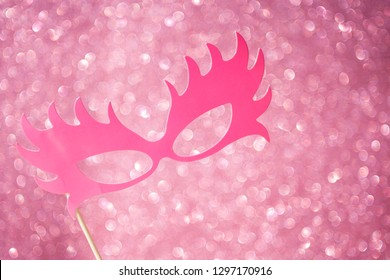 Carnival mask on a pink background with the effect of shining golden glitter. Holiday card. Carnival. Mardi gras. Masquerade. Empty place for festive text. Postcard, banner for Valentine's Day. Love s