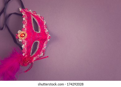 Carnival mask on purple background with copy space