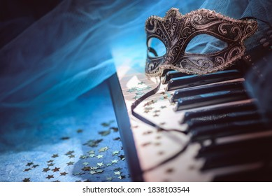 Carnival mask and piano keyboard with star-shaped confetti.