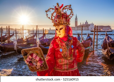 Carnival masks with mirror against dondolas in Venice, Italy