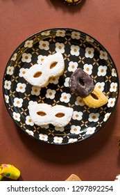 Carnival masks of short pastry with different decoration on a plate with whistlers around on a brown  background