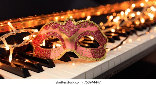 Carnival and music. Carnival mask and lights on a classical piano keyboard