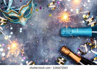 Carnival or new year celebration background. Champagne bottles and party accessories. Copy space