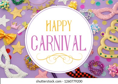 carnival party celebration concept with masks and colorful party accessories over pink, purple wooden background. Top view