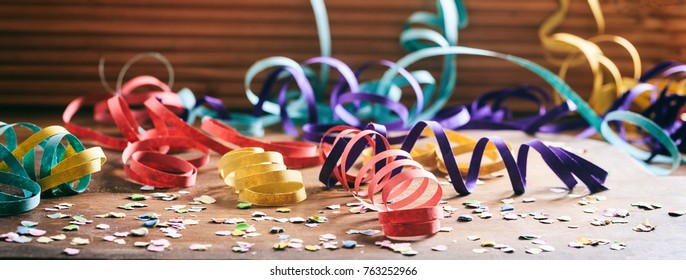 Carnival party concept. Colorful confetti and serpentines on wooden floor background