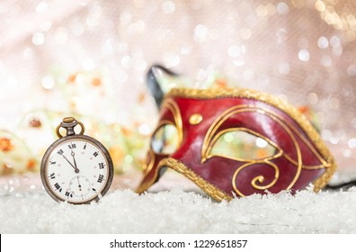 Carnival party countdown. Minutes to midnight on an old watch, red venetian mask, bokeh festive background