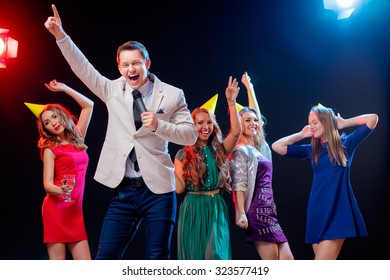 Carnival and party. Emcee with microphone. Group of cheerful friends dancing in nightclub.