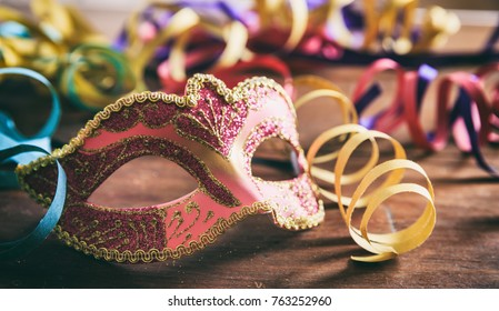 Carnival party. Mask and serpentines on wooden background, front view