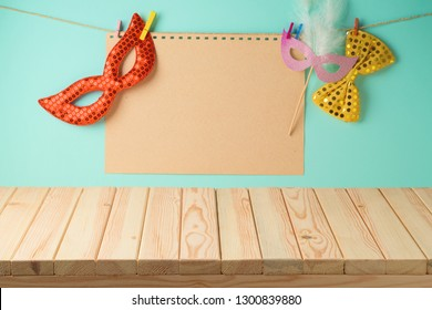 Carnival or purim holiday background with empty wooden table, paper note and carnival mask.