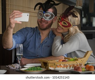 Carnival selfie couple at sushi restaurant wearing carnival mask.