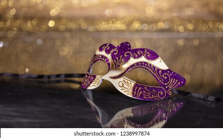 Carnival time. Venetian mask on golden bokeh background, reflections, copy space