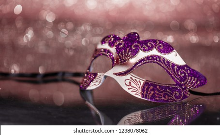 Carnival time. Venetian pink mask on pink bokeh background, reflections, copy space