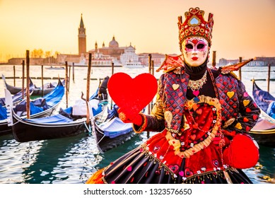 Carnival of Venice, beautiful mask at Piazza San Marco with gondolas and Grand Canal, Venezia, Italy.