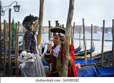 Carnival in Venice. A couple in costumes on the wooden bridge at channel shore. Gondola and Lantern on the background. Valentine's Day