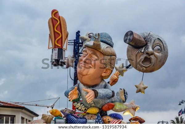 "Carnival of Viareggio VIAREGGIO , TUSCANY, ITALY - FEBRUARY 09 2019: First day of parade floats in the main avenue of Viareggio, medium   shot of entitled wagon "" Moon dream, with Donald Trump"
