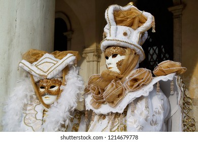 Carnival white-gold mask and costume at the traditional festival in Venice, Italy