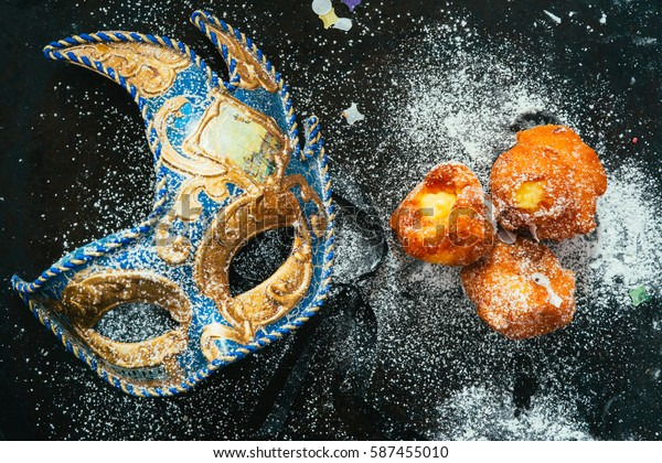 """Carnivalesque composition. Top view of italian fried carnival dessert called """"frittelle"""" with creme and chocolate icing sugar with an elegant carnival mask over a black background with icing sugar."""