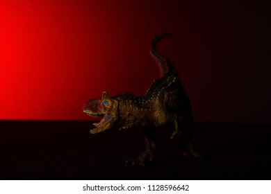 carnotaurus with spot light on the head and red light on background