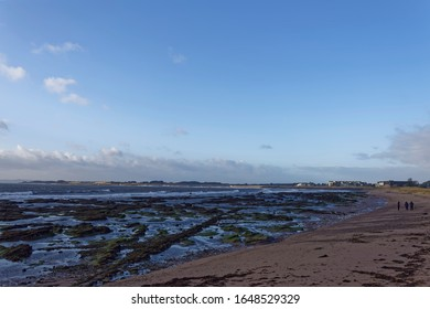 Carnoustie, Scotland - 16th February 2020: The rocky North Beach at Carnoustie with the tide out and People walking on the Beach.