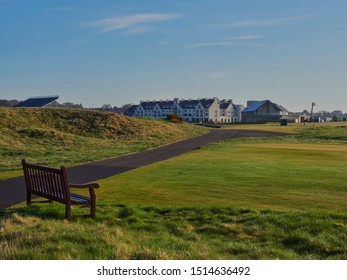 Carnoustie, Scotland - 1st May 2018: A Wooden Bench looking over to Links House and the Carnoustie Golf Hotel around the 1st Tee and 18th Green. Carnoustie, Angus, Scotland.
