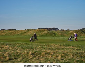 Carnoustie, Scotland - 1st May 2018: Three Golfers striding up the 3rd Fairway at Carnoustie Golf Links in a brisk Breeze. Carnoustie, Angus, Scotland.