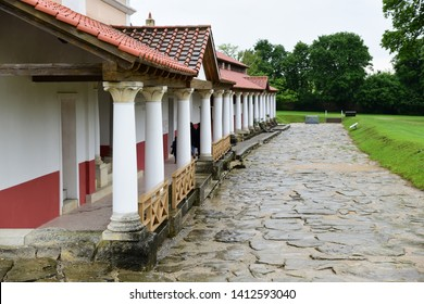 Carnuntum, Lower Austria - May, 2019: Fully reconstructed houses with columned hall along cobbled street built above the archaeological excavations of the civilian city of the Roman province Pannonia.