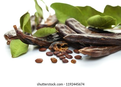 Carob bean. Healthy organic sweet carob pods with seeds and leaves on white background