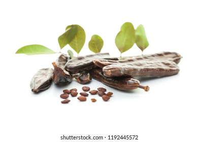 Carob bean on white. Healthy organic sweet carob pods with seeds and leaves, healthy eating and food background.