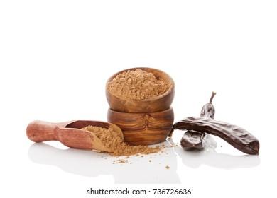 Carob bean,  pod and carob powder isolated on white background. Healthy cocoa alternative.
