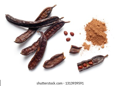 Carob bean pods, seeds and powder on white background