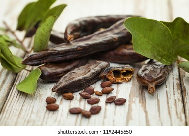 Carob beans. Healthy organic sweet carob pods with seeds and leaves on a wooden board. Healthy eating, food background.
