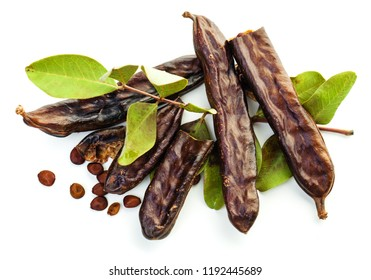 Carob beans. Healthy organic sweet carob pods with seeds and leaves on white background