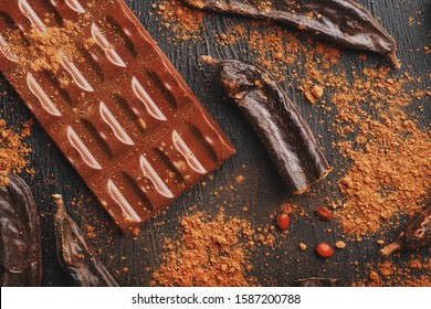 Carob chocolate and carob fruit powder on dark background. A tasty and useful substitute for chocolate. Health benefits. Soft contrast