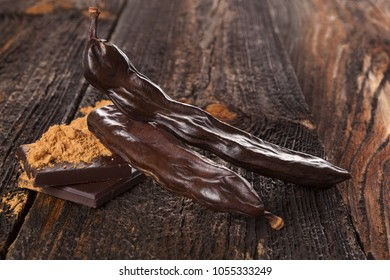 Carob chocolate and sweets, carob powder on wooden background.