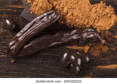 Carob chocolate, sweets and carob powder on wooden background.
