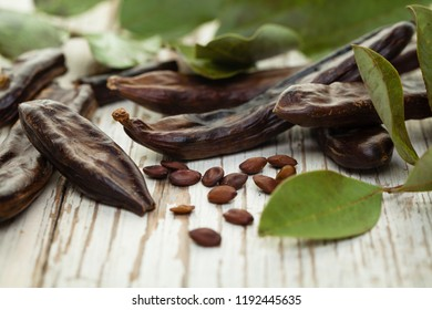 Carob, healthy eating and food background. Healthy organic sweet carob pods with seeds and leaves on a wooden table.