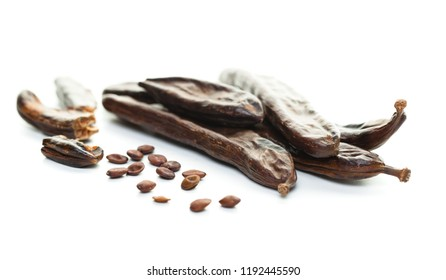 Carob. Healthy organic carob pods with seeds on white background