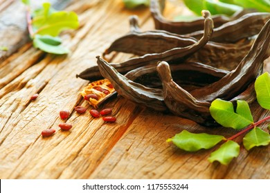 Carob. Healthy organic sweet carob pods with seeds and leaves on a wooden table. Healthy eating, food background.