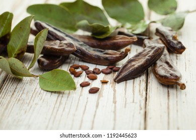 Carob. Healthy organic sweet carob pods with seeds and green leaves on a wooden board. Healthy eating, food background.