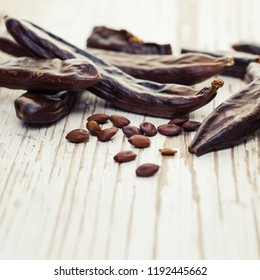 Carob. Healthy organic sweet carob pods and seeds on white wooden background closeup.