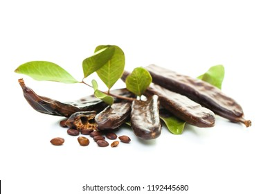 Carob. Healthy organic sweet carob pods with seeds and leaves on white background