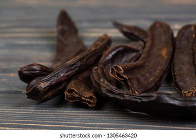 Carob. Healthy organic sweet carob pods on gray wooden background closeup.